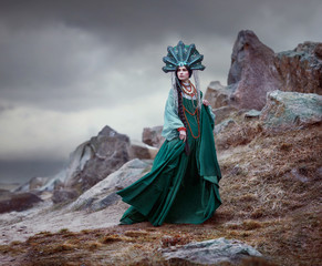 A woman in a green gown on a mountain.