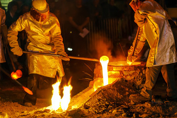 Workers melting steel to produce a bell in the traditional way.
