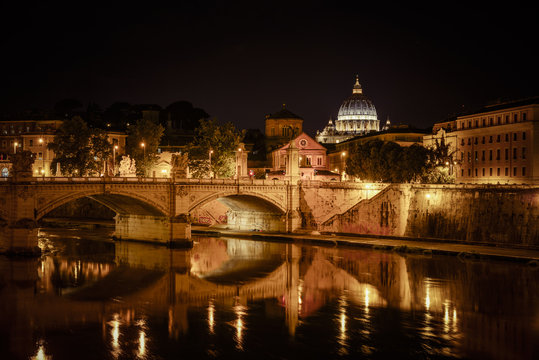 Basilica of San Pietro at night overlooking the Tevere river and surrounding historical landmarks of Rome.