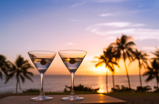 Pair of martini glasses and a beautiful beach sunset.
