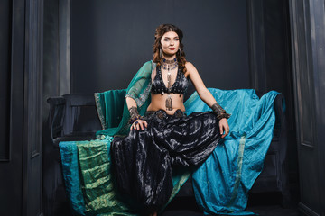 East image of a beautiful young girl, dressed in a traditional oriental costume for belly dancing.