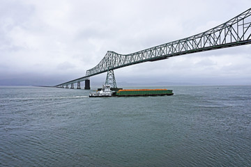 Wall Mural - pusher tug and barge heading up the Columbia river and passing under the Astoria-Megler bridge