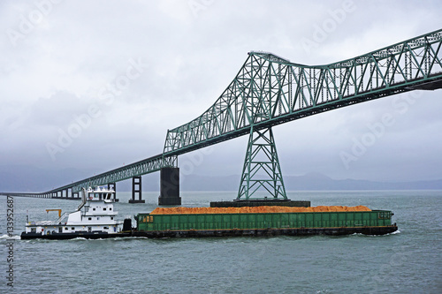 Wall mural pusher tug and barge heading up the Columbia river and passing under the Astoria-Megler bridge