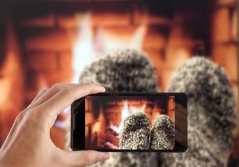 Hand making photo Feet in woollen socks by the fireplace.