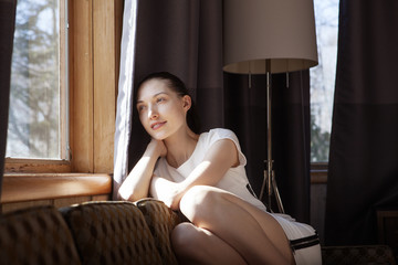 Thoughtful woman looking through window while sitting on sofa at home