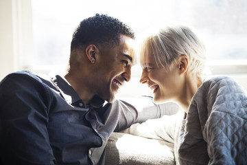 Happy couple looking at each other while sitting on sofa