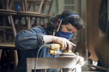 Carpenter sanding wooden chair at workshop