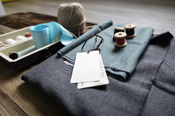 Fabric with sewing equipment on wooden table