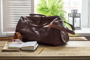 Leather bag and books on table at home office by window