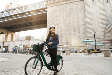 Woman with bicycle on city street against bridge