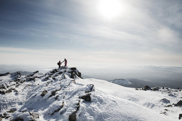Friends hiking on snow covered mountain against sky