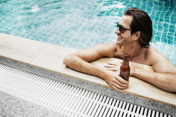Happy man holding beer bottle in swimming pool