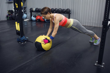 Full length of female athlete leaning on medicine ball at gym
