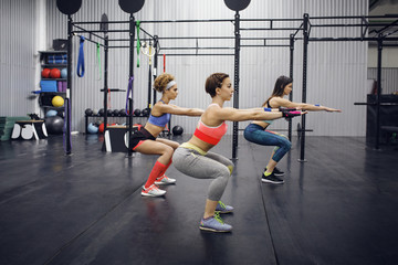 Side view of confident female athletes exercising in health club