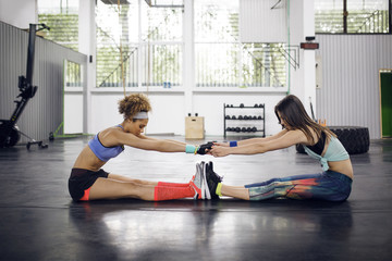 Side view of female athletes exercising while sitting on floor in gym