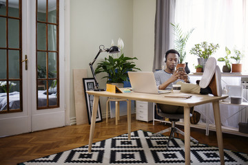 Relaxed man using smart phone at home office