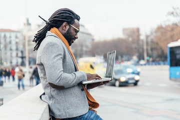 Businessman using his laptop in the Street.