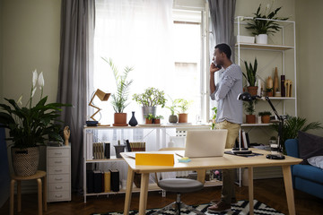 Side view of businessman talking on smartphone at home office