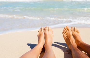 Romantic beach holiday. Couples feet on the beach.