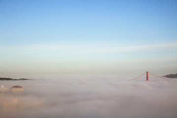 Majestic view of clouds covering Golden Gate Bridge against blue sky