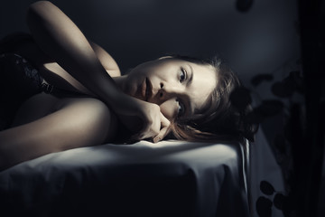 Thoughtful woman lying on bed at home