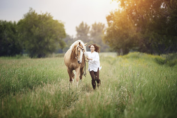 Mid adult woman and horse running on grassy field at countryside