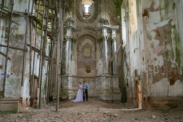 Young bride in a wedding dress standing on the balcony and looking at a beautiful bouquet in an abandoned church
