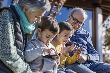 Happy grandparents and grandsons using smart phones in park