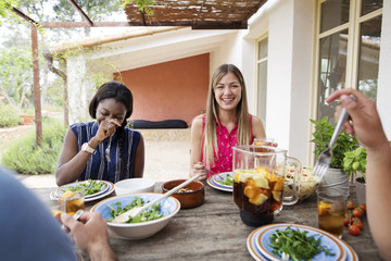 Happy woman having lunch with friends at outdoor table