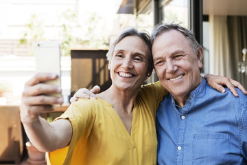 Cheerful senior couple taking selfie through smart phone at porch