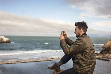 Side view of man taking picture of sea through smartphone