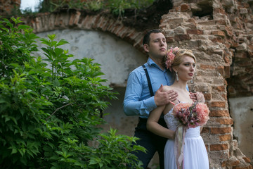 Young bride in a wedding dress hugs groom on the background of the old ruined church