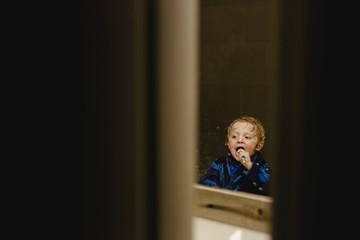Boy brushing teeth reflecting on mirror seen through doorway
