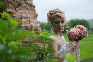 Young bride in a wedding dress with a bouquet of beautiful look into the lens