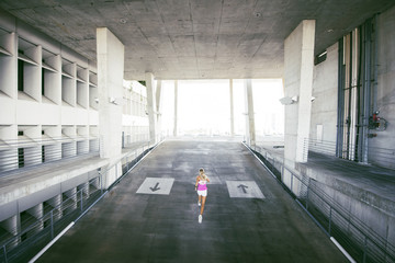 High angle view of sporty woman running in parking lot