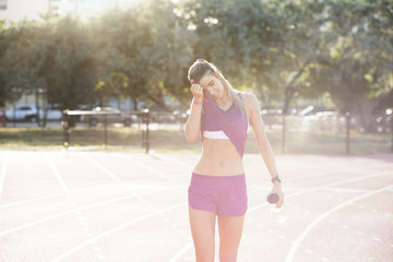Tired female athlete wiping sweat on field