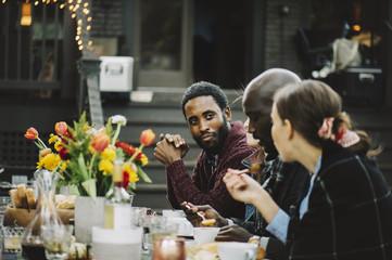 Friends talking while having pumpkin soup in backyard