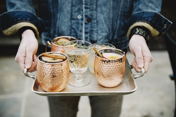 Midsection of man carrying drinks in serving tray