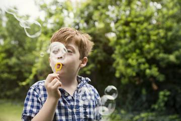 Thoughtful boy blowing bubbles in yard
