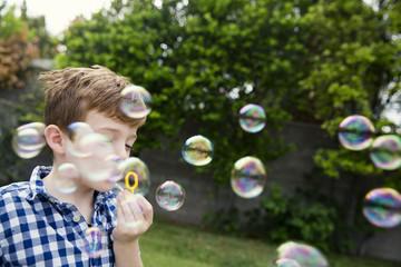 Boy blowing bubbles in yard