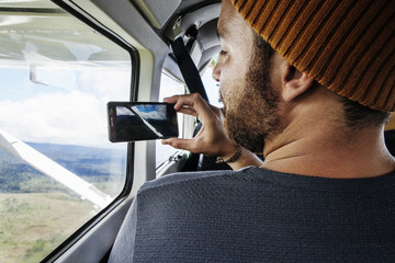 Rear view of man taking photograph through smartphone from airplane window