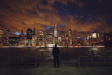 Rear view of man looking at illuminated skyline during night