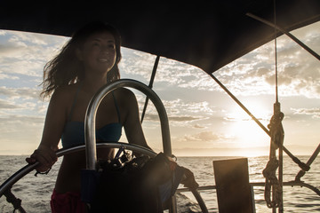 Happy woman standing in boat on sea against sky during sunset