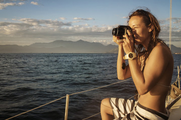 Woman photographing while sitting in boat on sea against sky