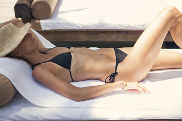 Side view of woman in black bikini lying on sunbed during summer vacation