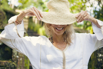 Happy woman wearing straw hat at park