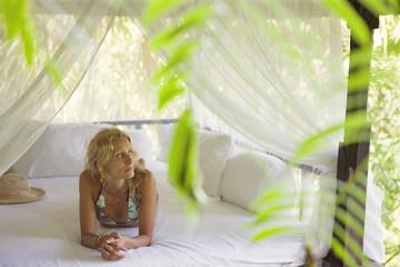 Thoughtful woman relaxing in gazebo