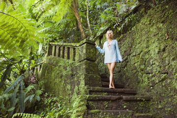 Thoughtful sensuous woman standing on mossy steps in forest