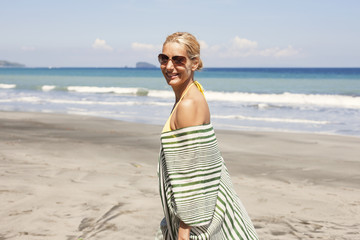 Portrait of happy woman standing on beach during summer vacation