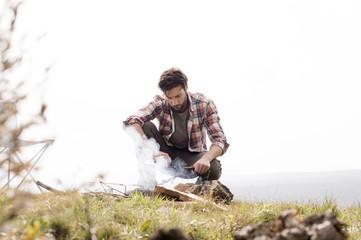 Man preparing tea on bonfire at campsite against clear sky